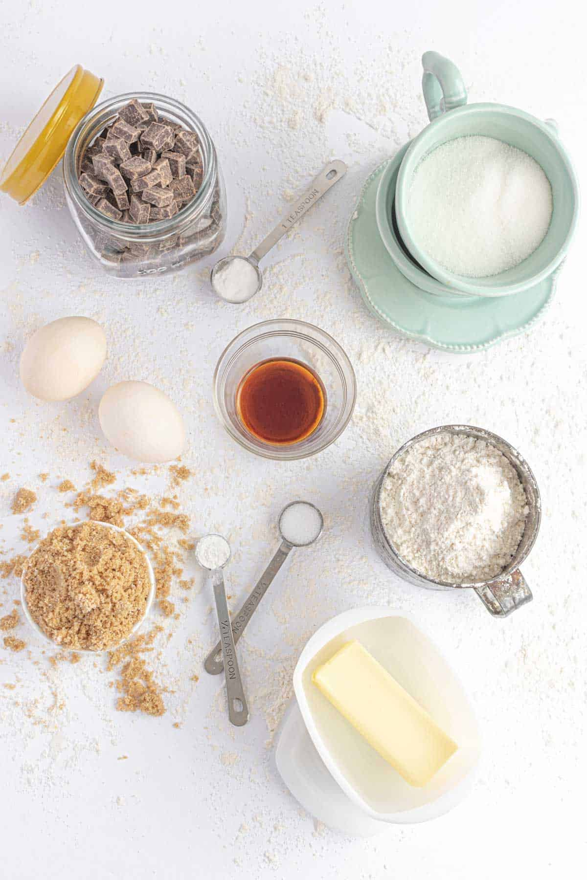 A Stick of Butter, White Sugar, Vanilla Extract and the Rest of the Ingredients on a Countertop Dusted with Flour