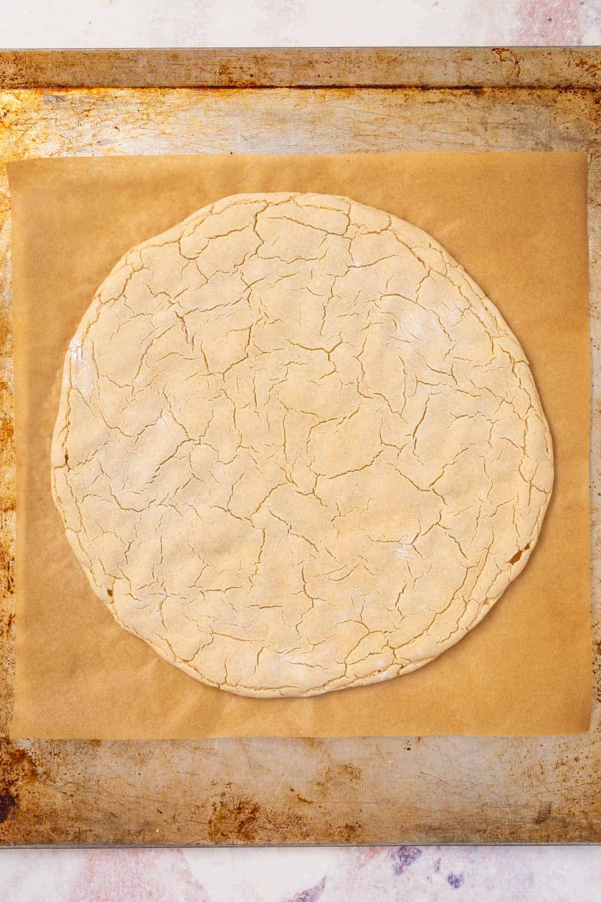 A Par-Baked Gluten-Free Pizza Crust on a Metal Pan Lined with Parchment Paper
