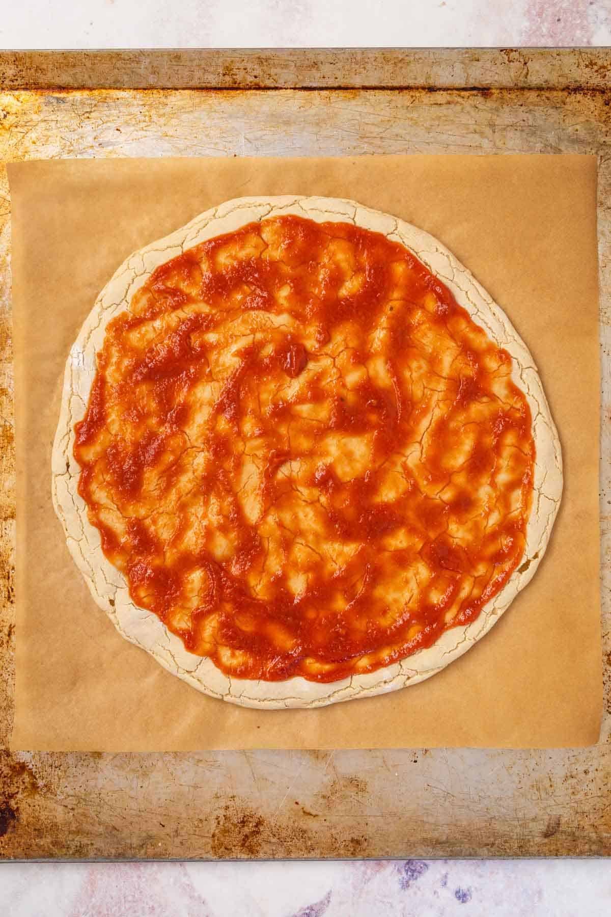 A Layer of Pizza Sauce Spread on Top of a Gluten-Free Pizza Crust