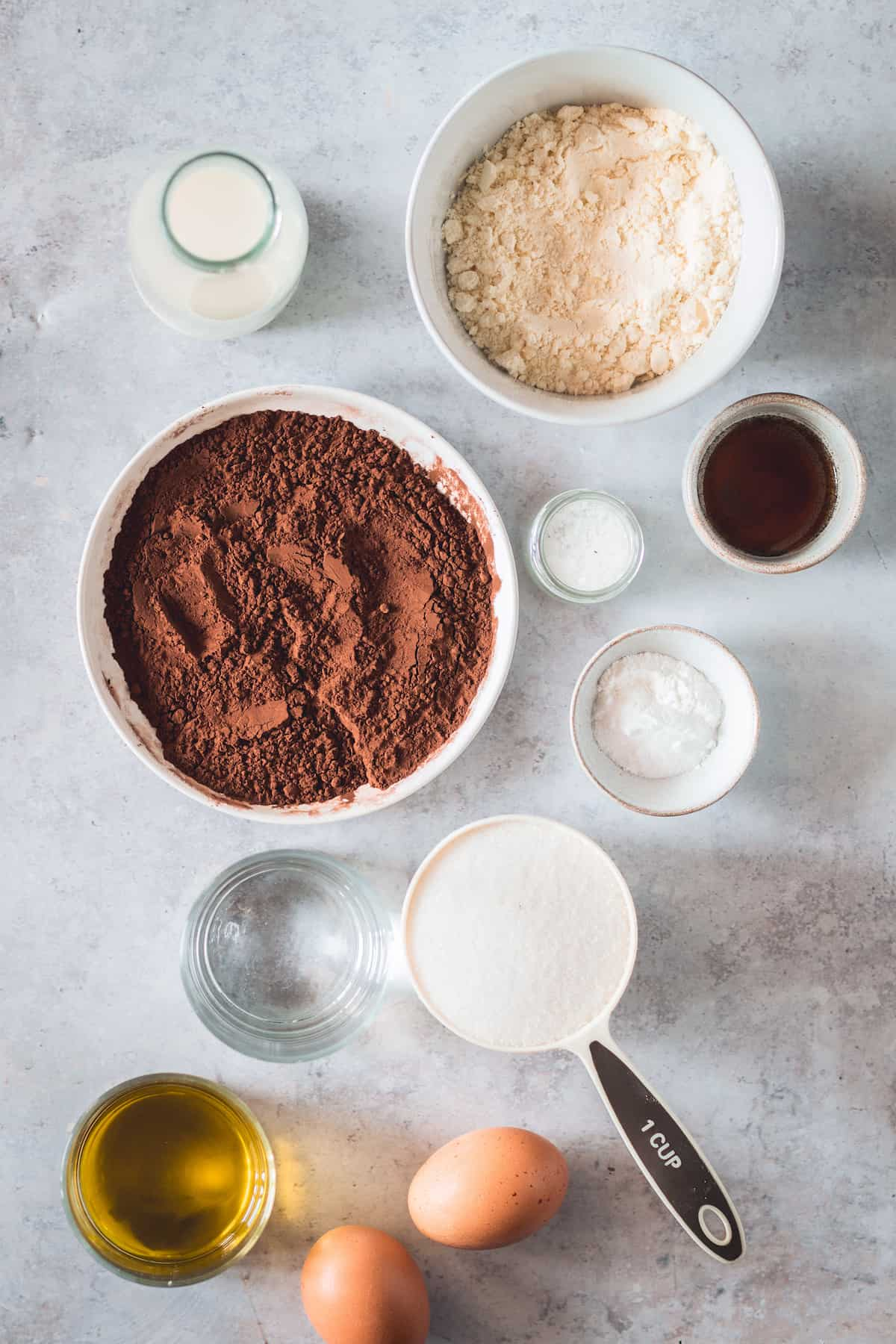 A Bowl of Cocoa Powder, A Bowl of Gluten-Free Flour, a Cup of Granilated Sugar, Two Eggs and the Rest of the Cupcake Ingredients on a Countertop
