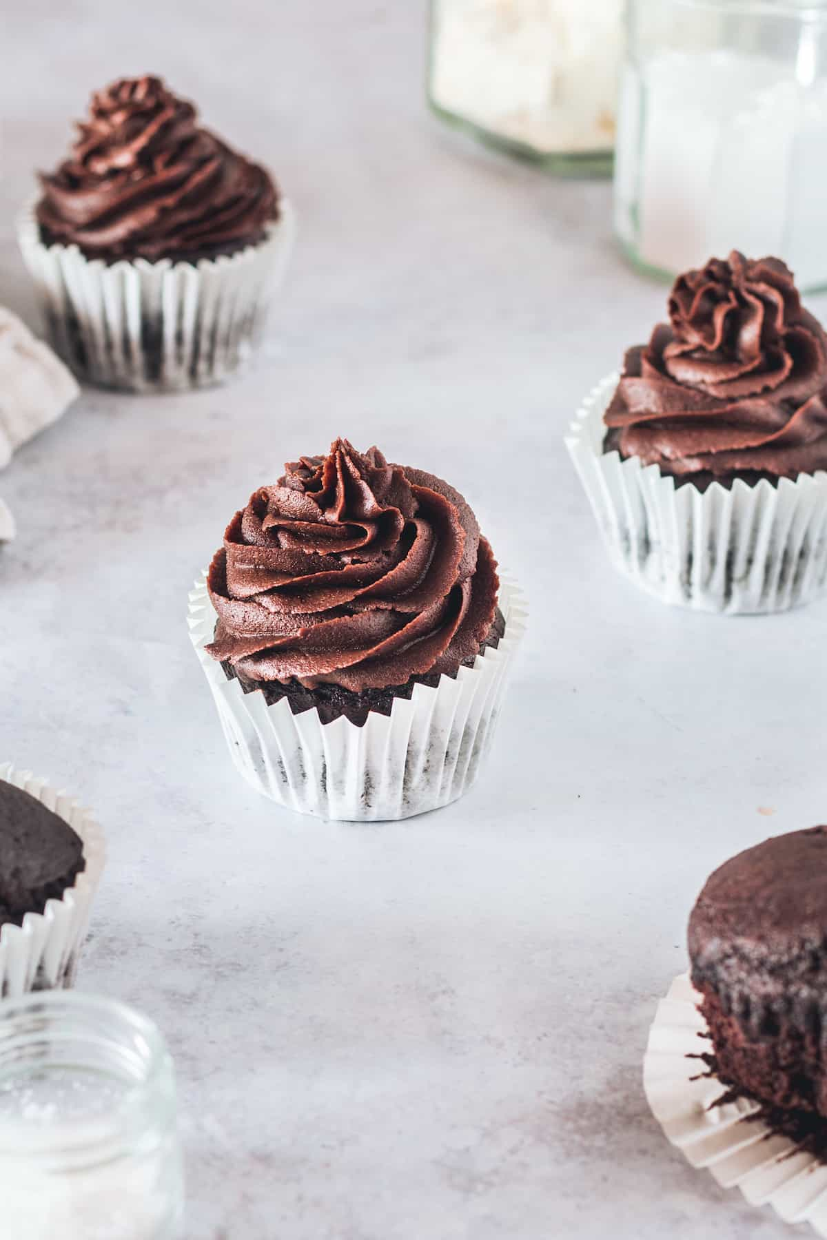 Frosted Chocolate Cupcakes on a Counter with Jars of Salt, Sugar and Gluten-Free Flour