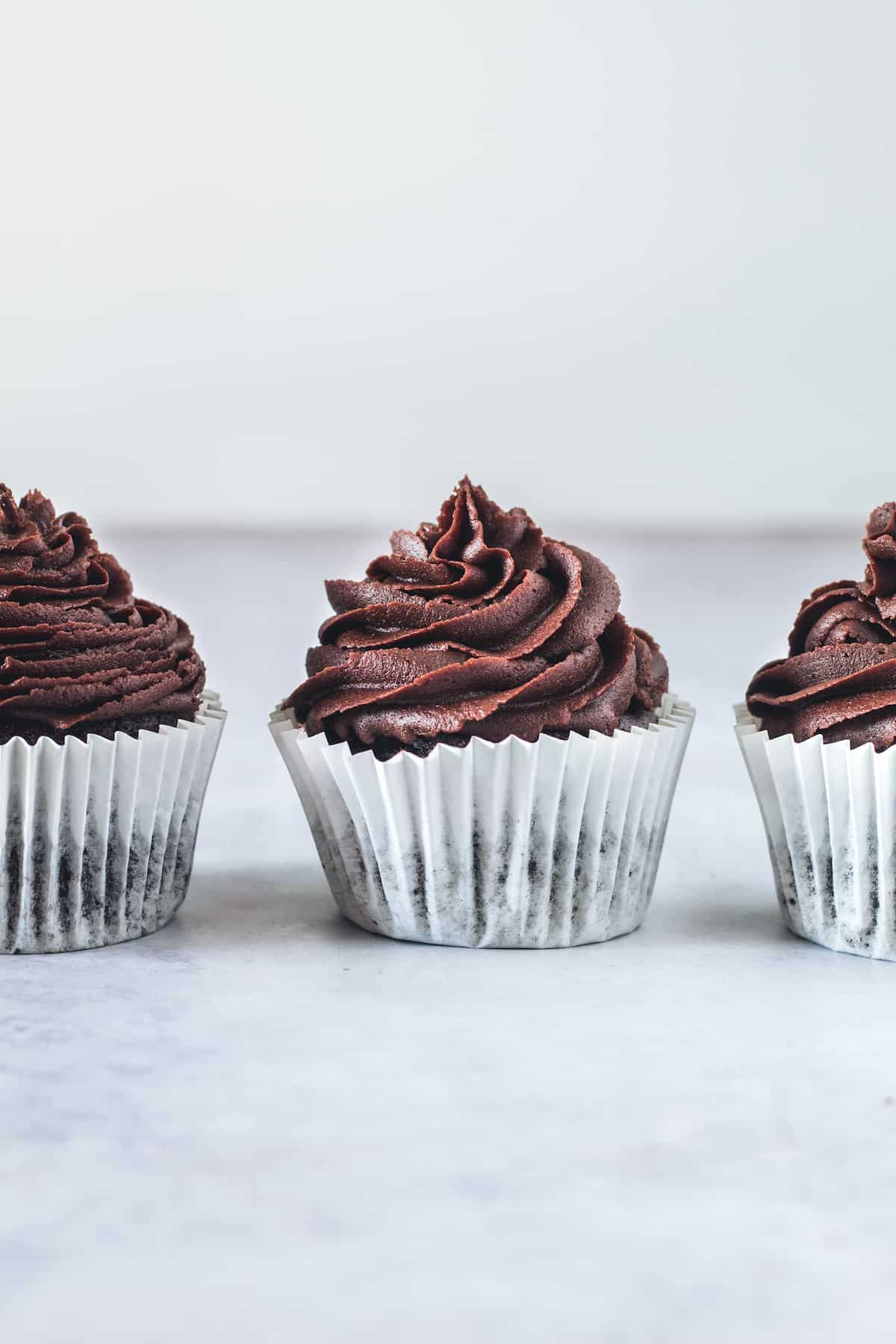 Three Gluten Free Chocolate Cupcakes Lined Up on a White Surface