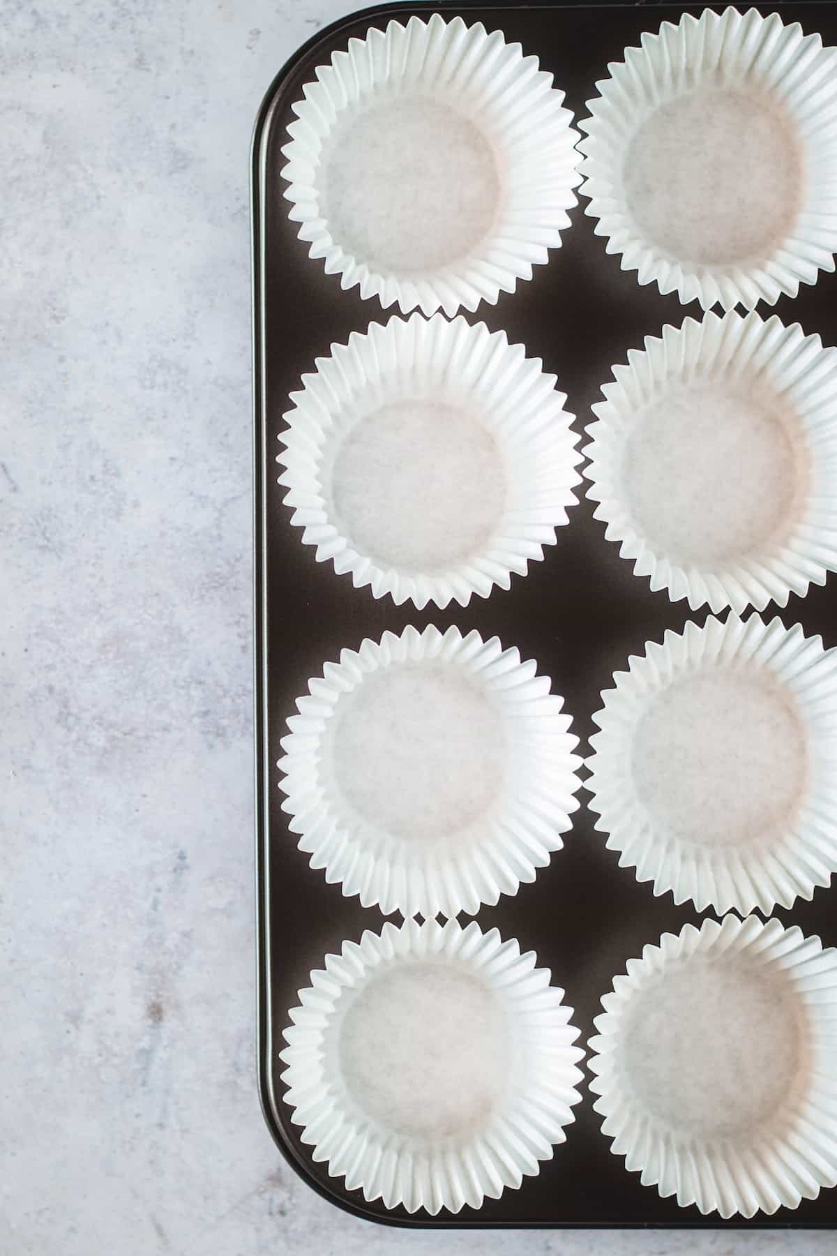 Eight White, Unfilled Cupcake Liners Inside a Metal Cupcake Pan