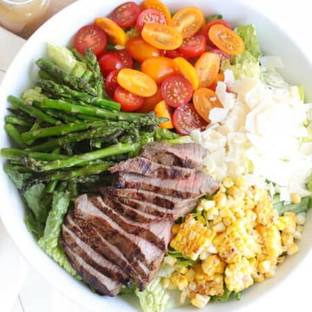 white bowl filled with a grilled steak salad with corn, asparagus, tomatoes, and shaved parmesan