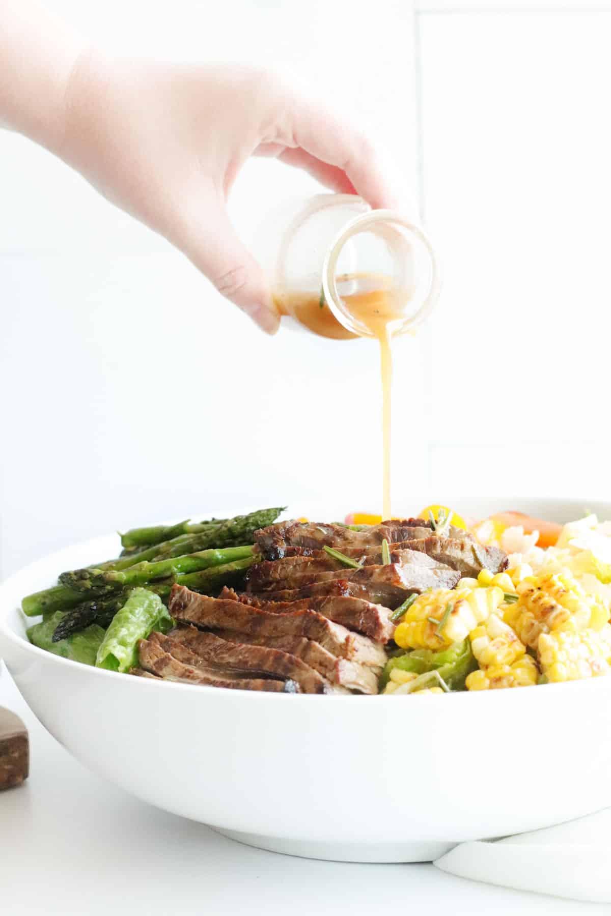 pouring salad dressing over a bowl of steak salad
