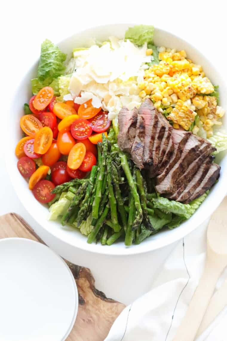 white serving bowl of grilled steak salad over romaine lettuce with tomatoes, parmesan and grilled asparagus and corn