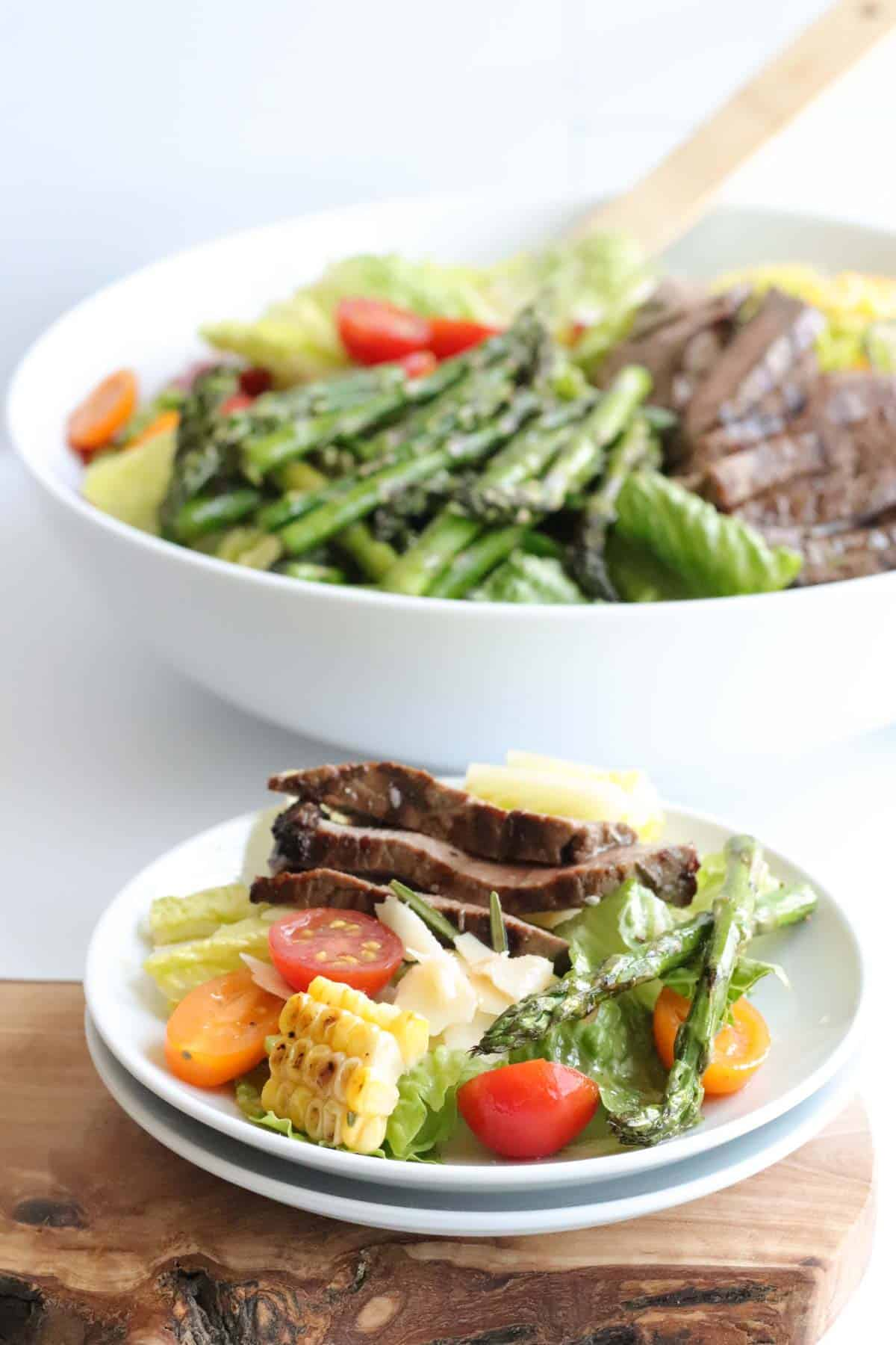 single serving of steak salad on a small while plate in front of the large serving bowl of salad