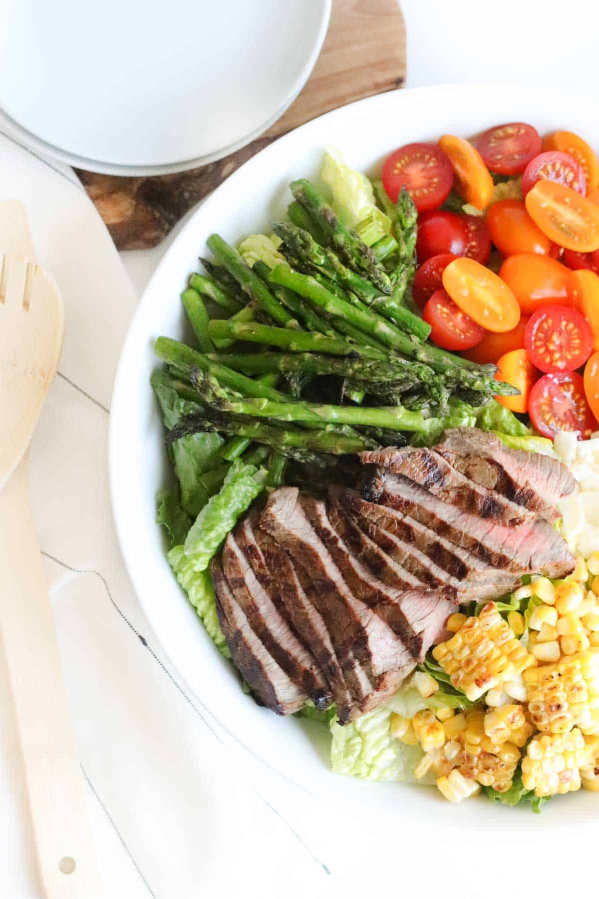 big white bowl of romaine topped with sliced grilled steak, grilled corn and asparagus, and halved tomatoes next to a stack of small white plates