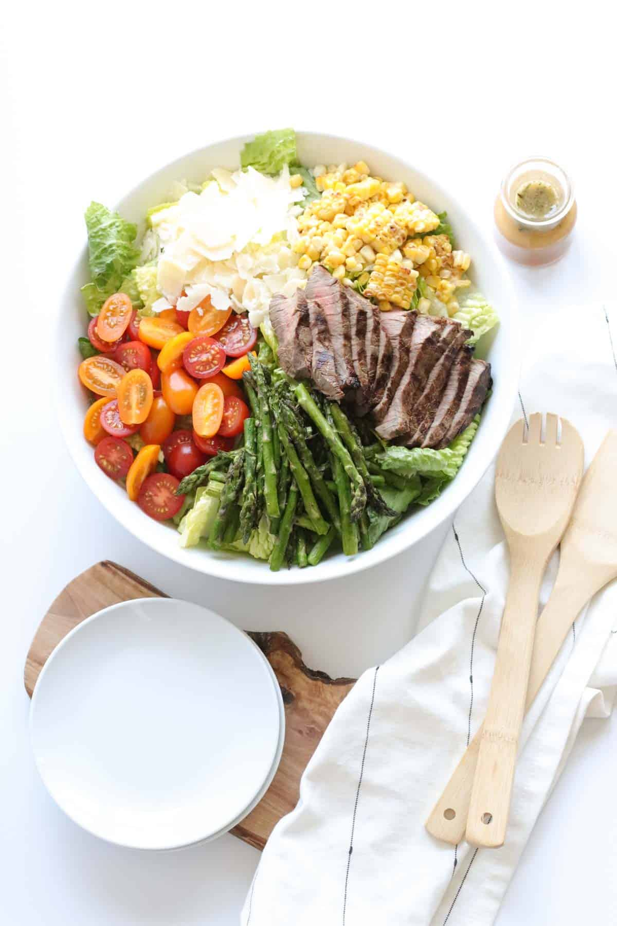 table set with serving bowl of grilled steak salad, wooden serving spoons, a stack of small white plates, and a bottle of salad dressing