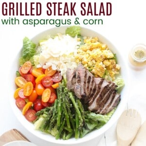grilled steak, corn, and asparagus with a small bottle of dressing next to it