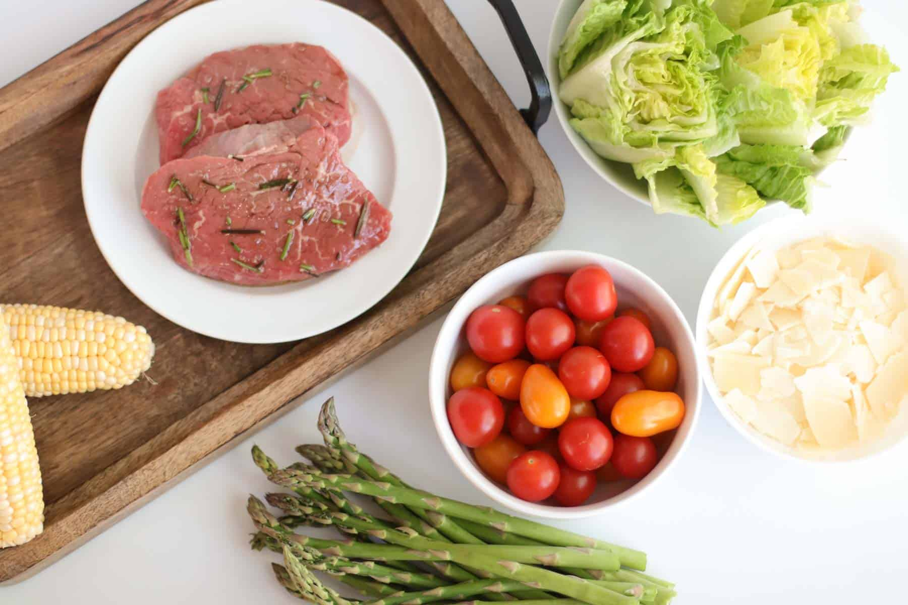 marinated steak, stacks of raw corn and asparagus, and bowls of chopped romaine, small tomatoes, and shaved parmesan