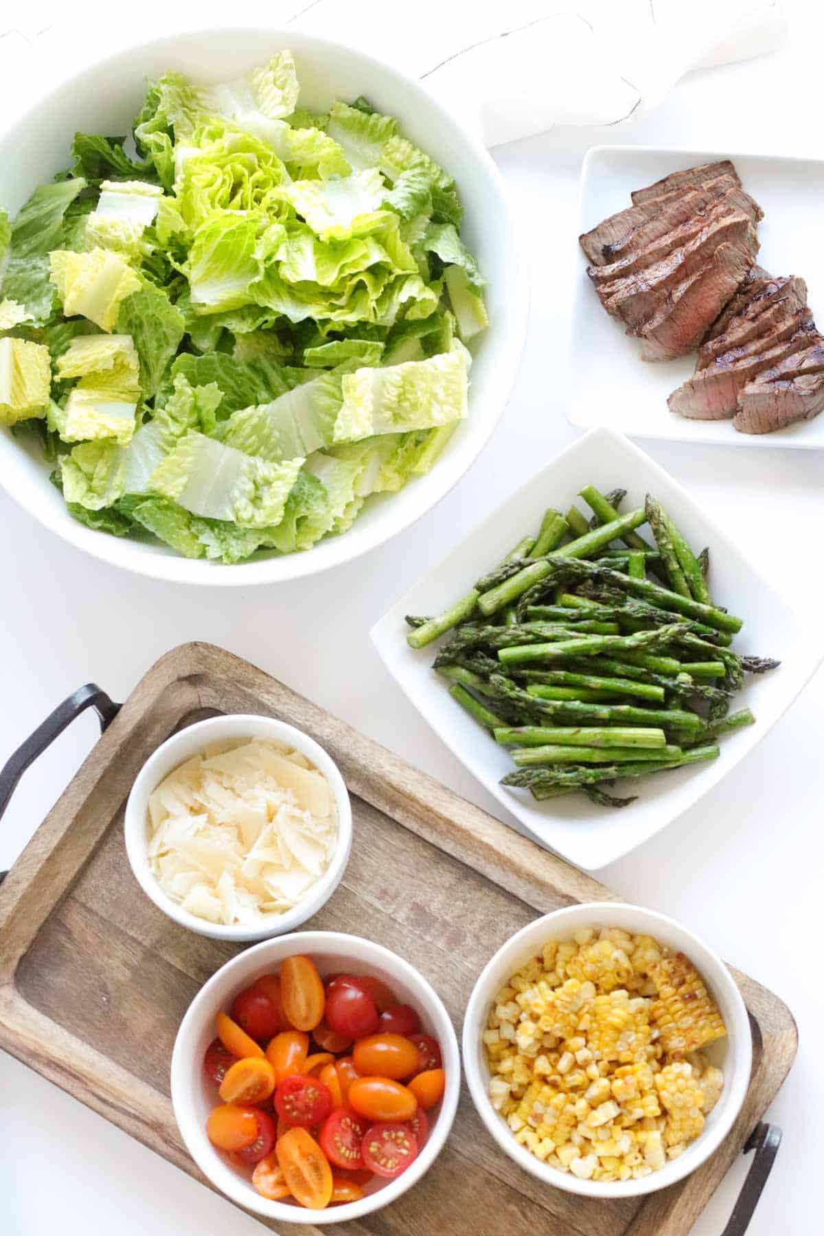 all of the different prepared salad components in bowls and on plates on a white table