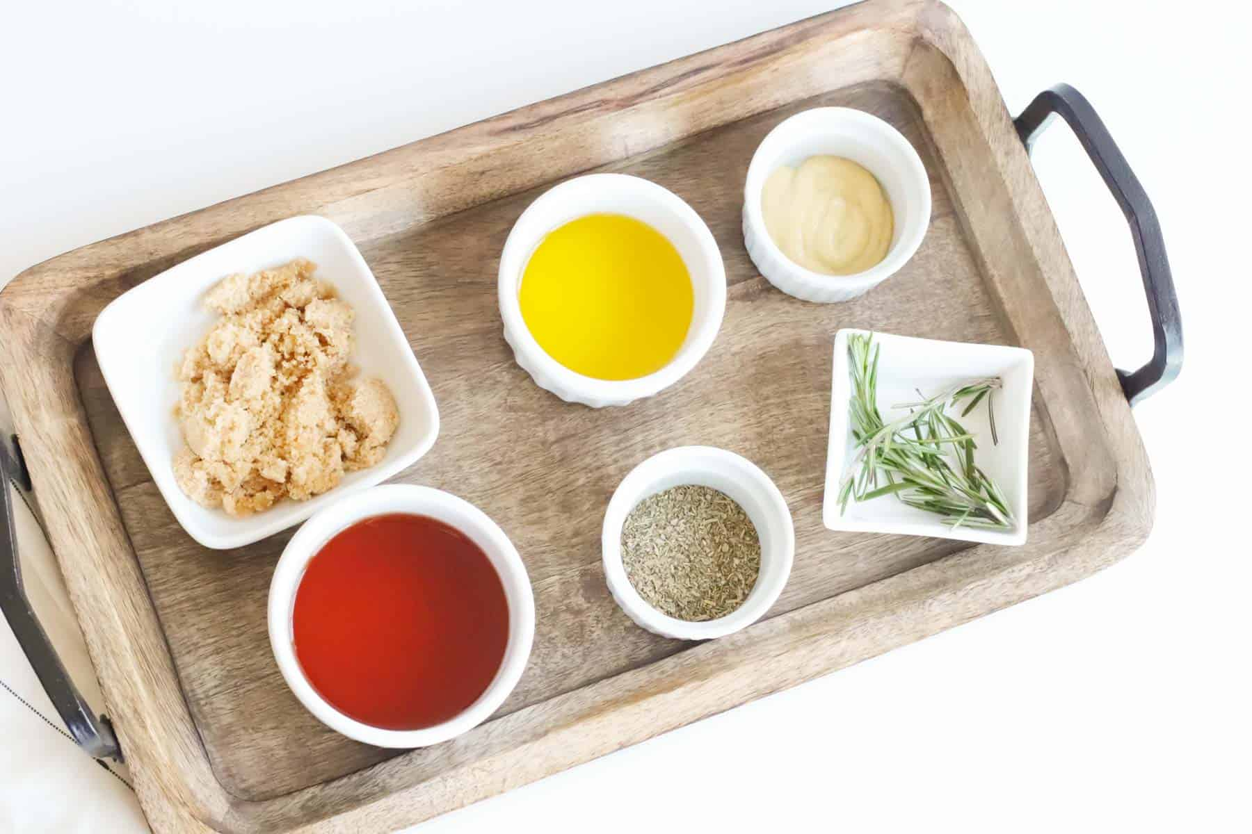 bowls of red wine vinegar, olive oil, dijon mustard, dried Italian seasoning, brown sugar, and fresh rosemary on a wooden serving tray