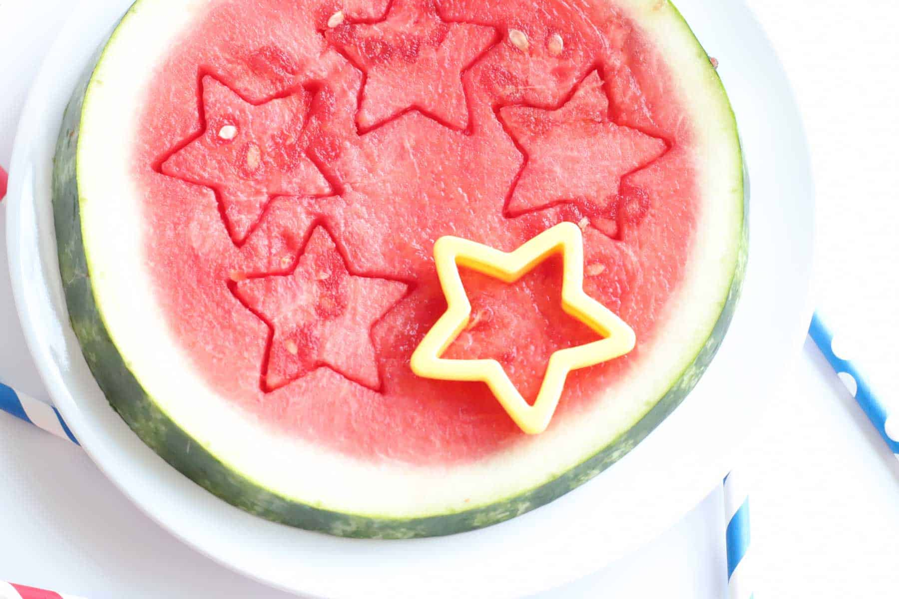 yellow star-shaped cookie cutter cutting stars out of a round slice of watermelon