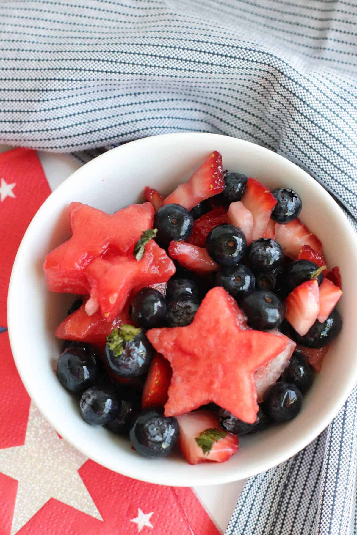 small bowl of fruit salad with chopped strawberries, blueberries, and watermelon stars surrounded by red ad white star napkins and a blue stripe cloth napkin