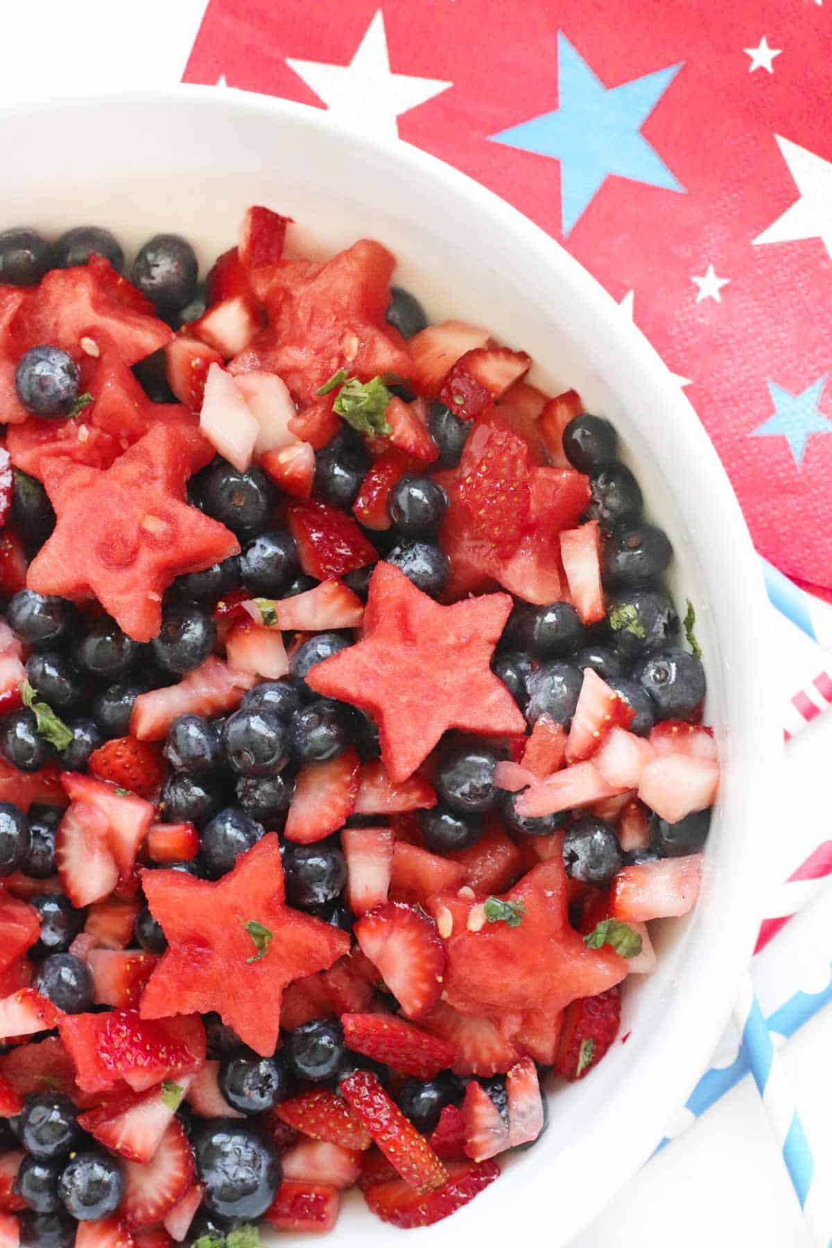 watermelon berry fruit salad in a white bowl surrounded by patriotic napkins and straws