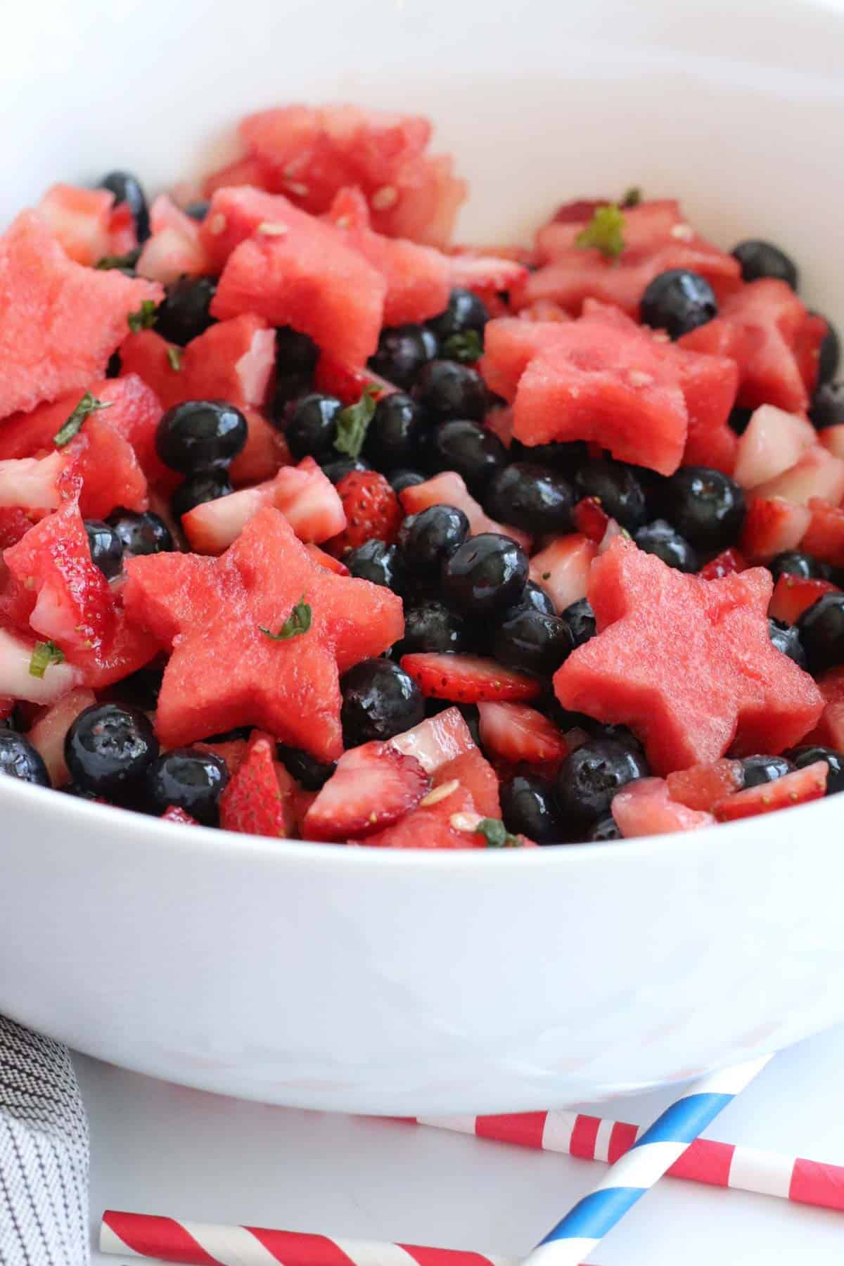 white bowl filled with a red, white, and blue berry fruit salad with strawberries, blueberries, and watermelon cut into star shapes