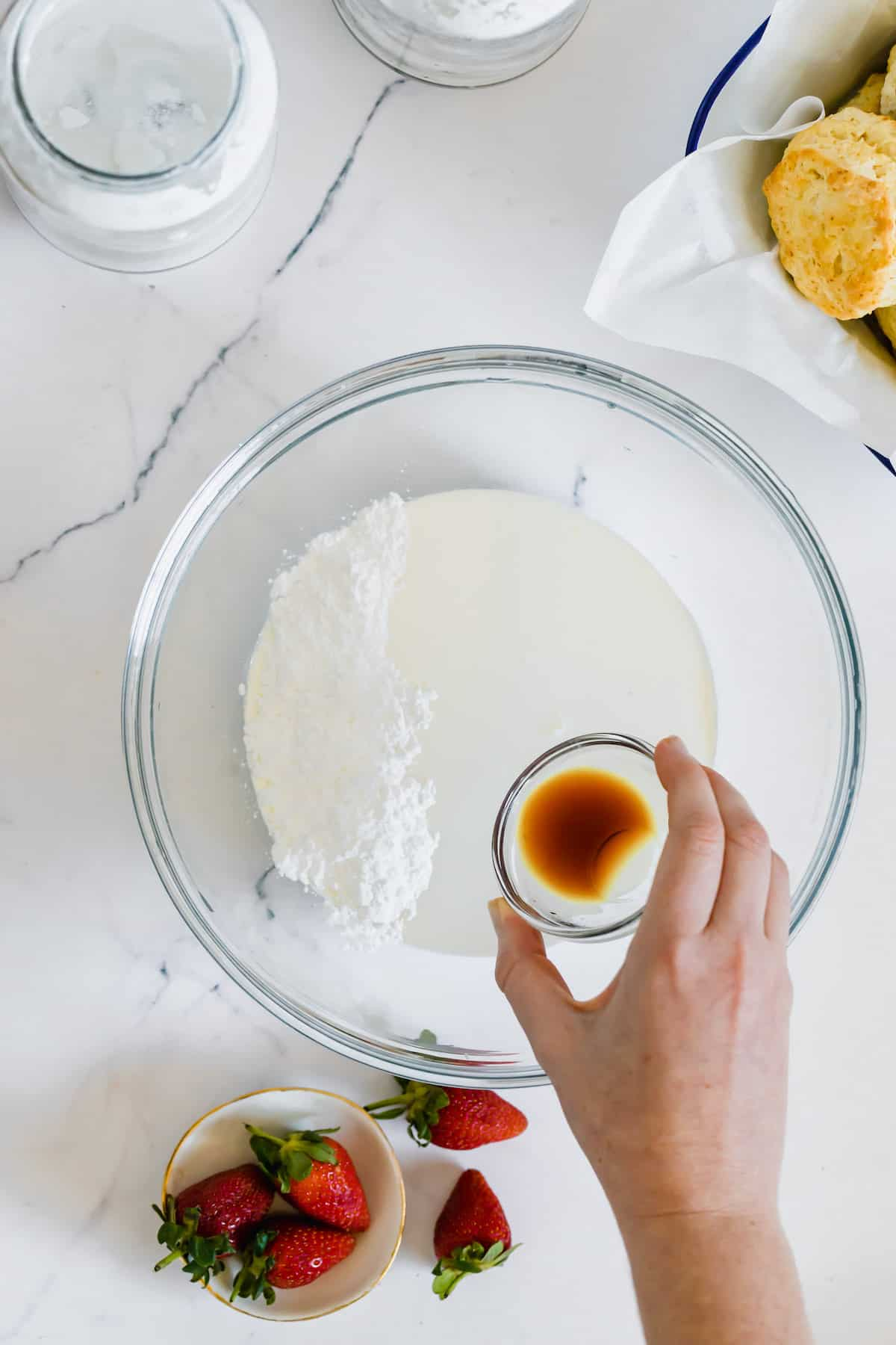 Vanilla Extract Being Added to a Bowl of Heavy Cream and Powdered Sugar