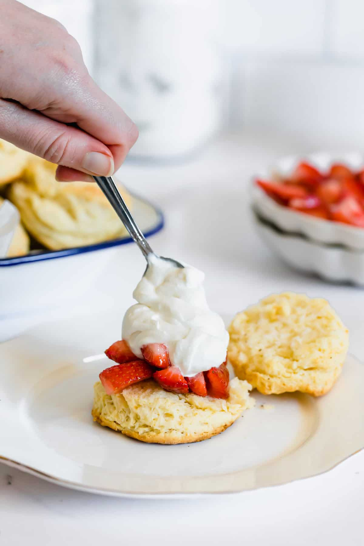 A Spoon Adding a Generous Dollop of Whipped Cream Over the Strawberry Filling on Half a Shortcake