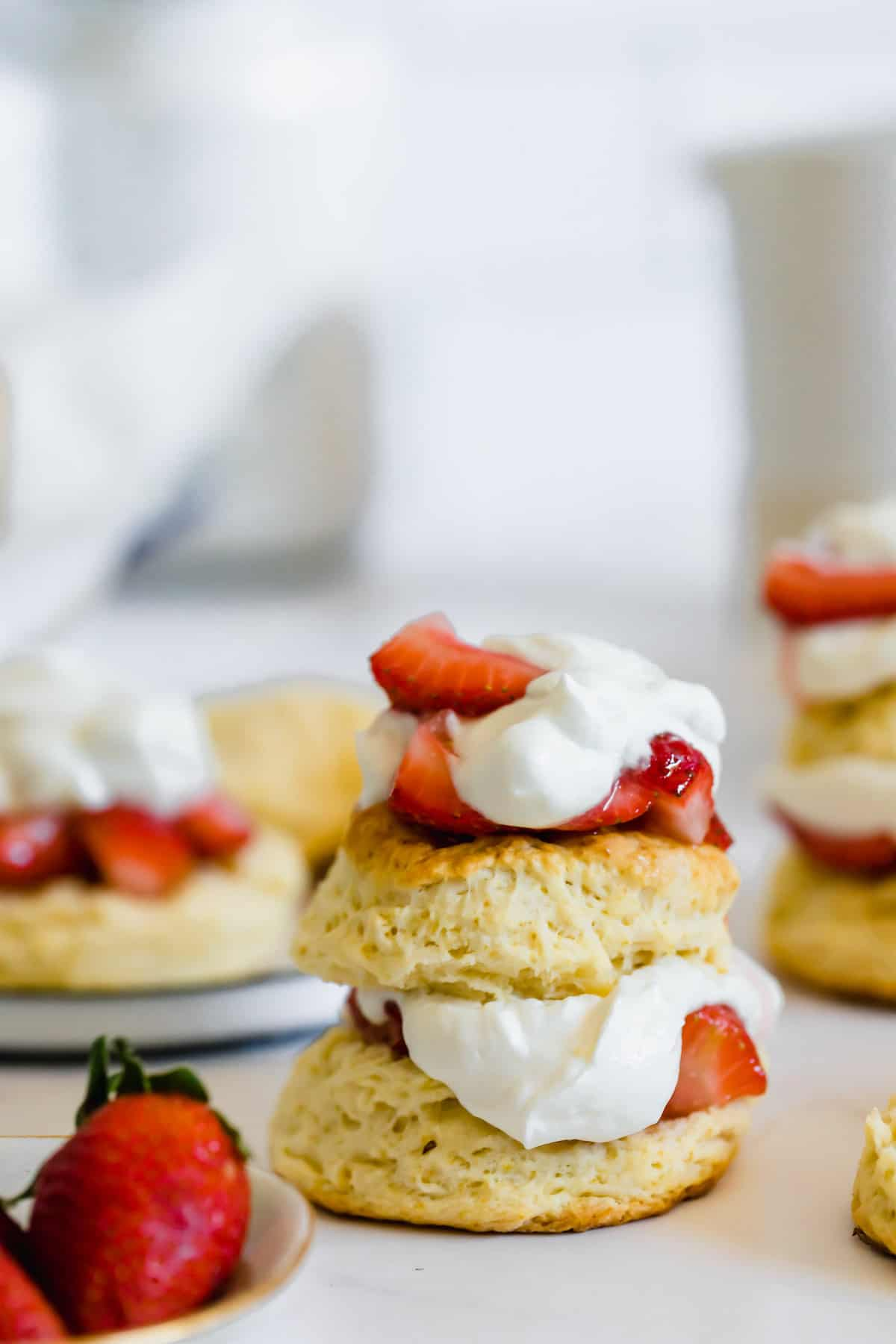 A Strawberry Shortcake Beside a Bowl of Fresh Berries and a Couple Other Shortcakes