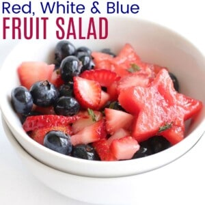 small bowl of berry watermelon fruit salad coated in a dressing with mint leaves