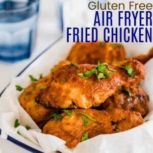 air fryer fried chicken stacked in a serving dish and garnished with parsley