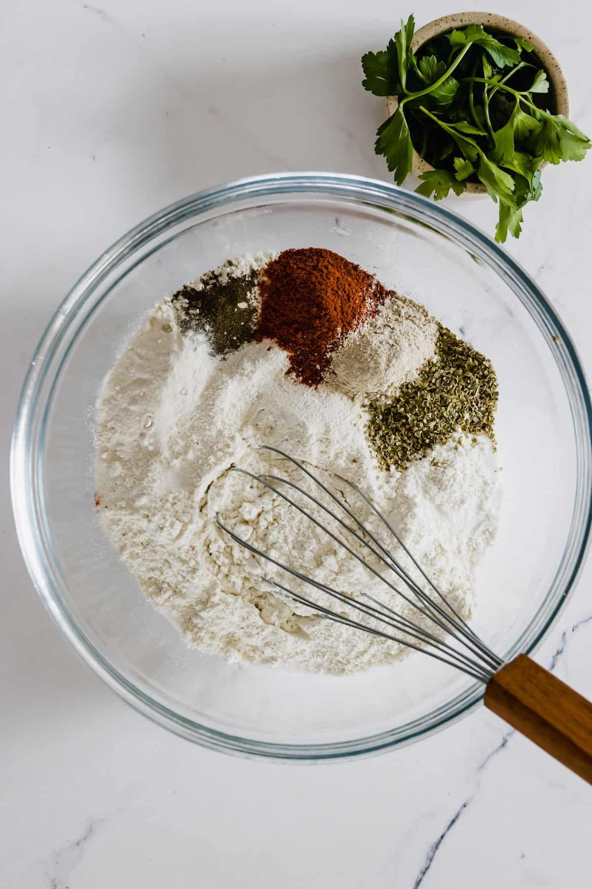 Flour, Salt, Pepper, Paprika, Garlic Powder and Onion Powder in a Glass Mixing Bowl