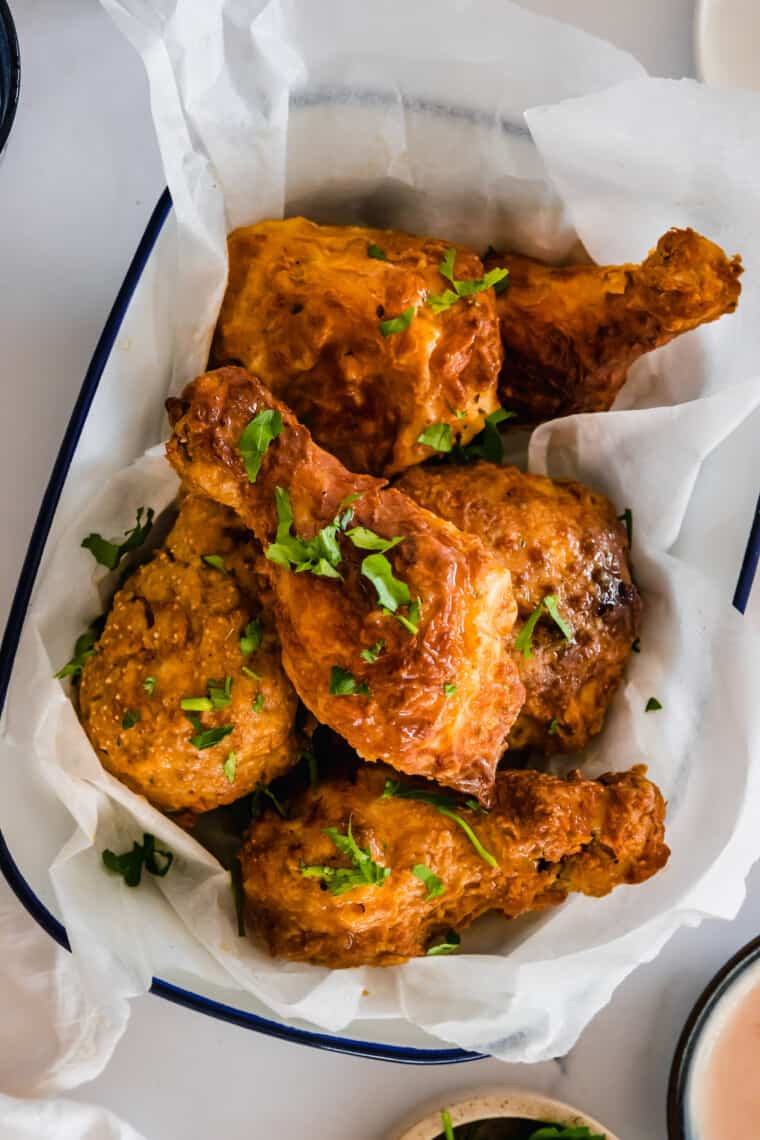 Six Pieces of Fried Chicken in a Serving Bowl Lined with Parchment Paper