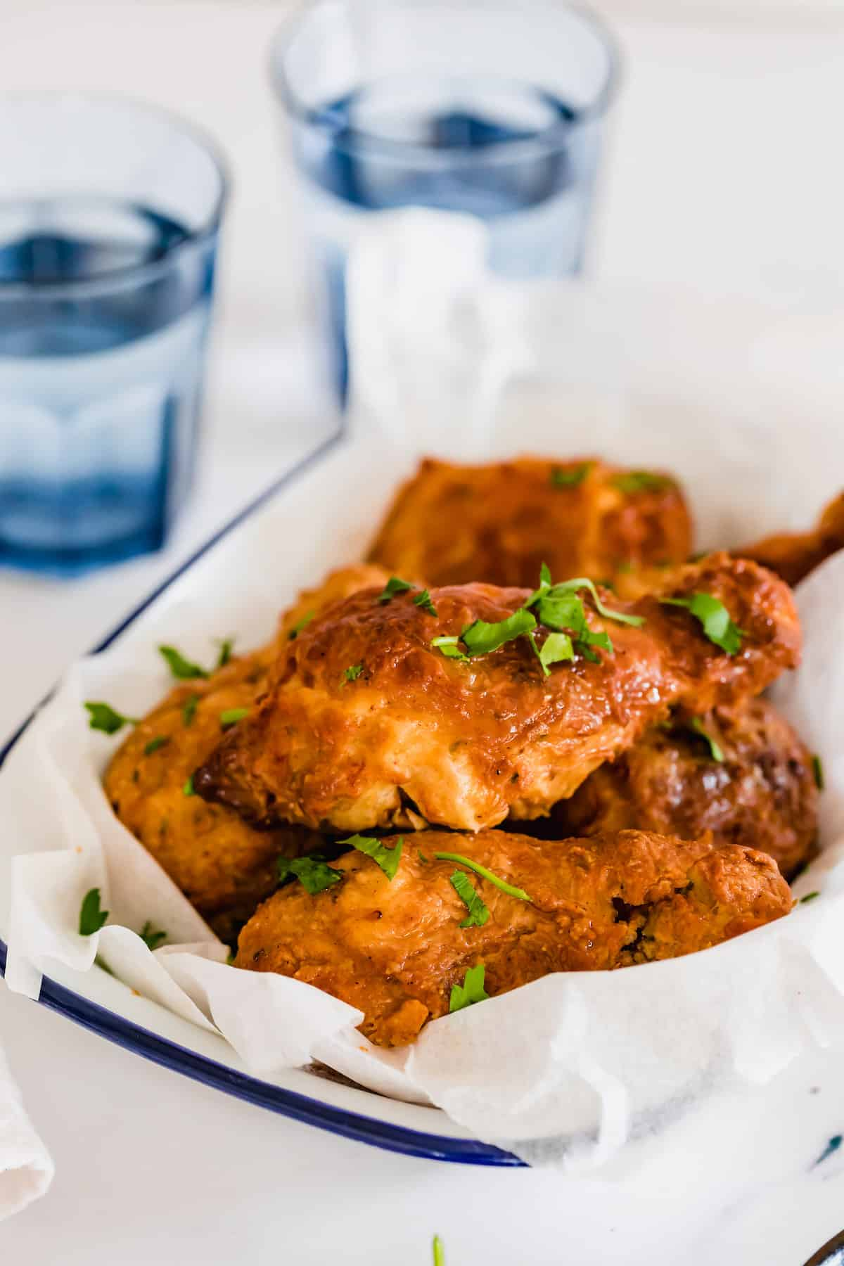 A Parchment-Lined Bowl of Air Fryer Fried Chicken in Front of Two Glasses of Water