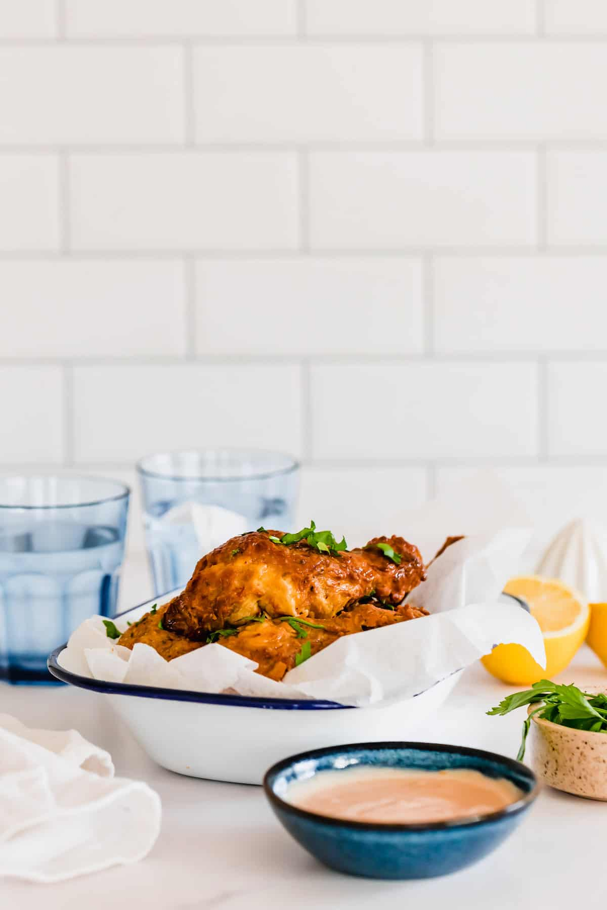 A White Brick Wall Behind a Setup of Fried Chicken, Dipping Sauce and Water