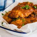 Air Fryer Fried Chicken Garnished with Fresh Chopped Parsley in a bowl lined with wax paper