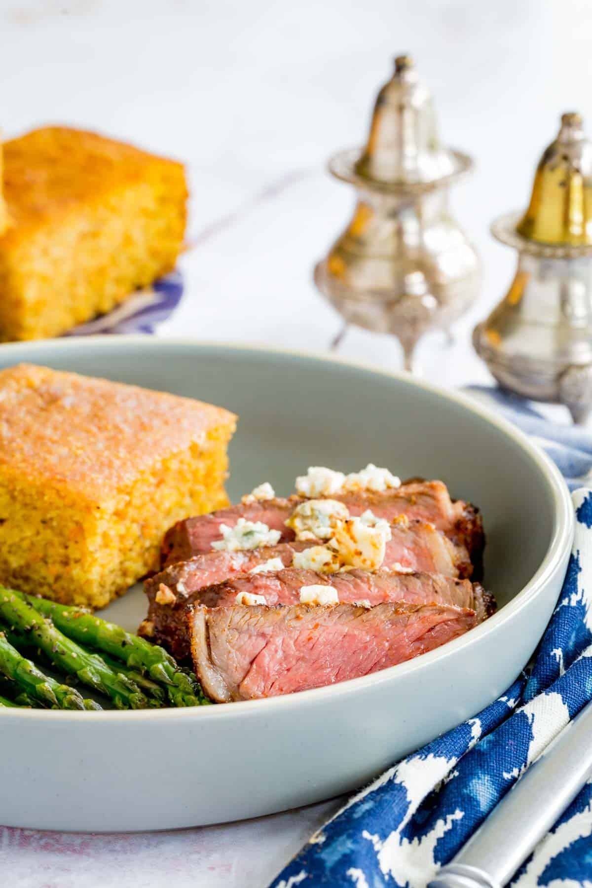 A Sliced-Up Black and Blue Steak Beside a Piece of Cornbread in a Bowl