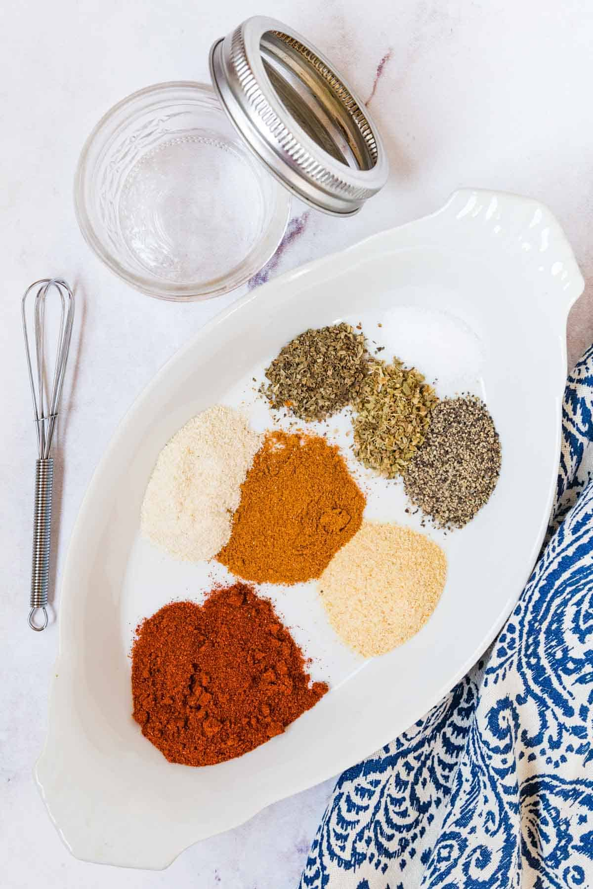 A Bowl Conaining All of the Spice Rub Ingredients Beside a Mini Whisk and a Glass Jar