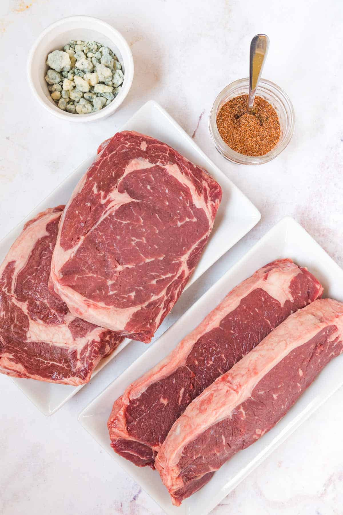 Four Raw NY Strip Steaks Beside a Bowl of Blue Cheese and the Spice Rub
