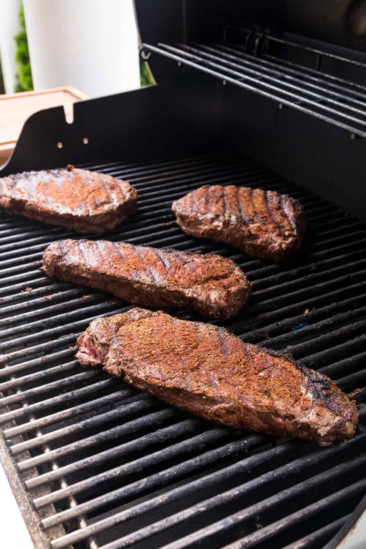 Four Blackened NY Stip Steaks Cooking Directly on the Grates of a Grill