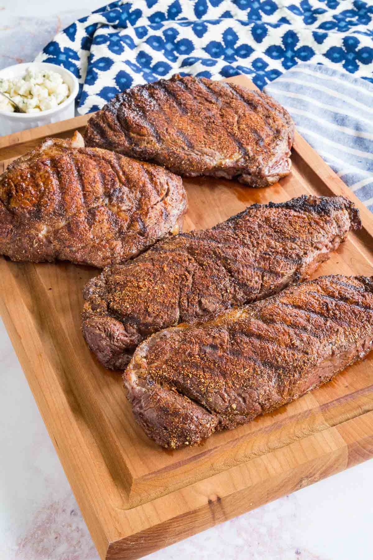 Four Black and Bleu Steaks on a Cutting Board Beside Two Blue Kitchen Towels