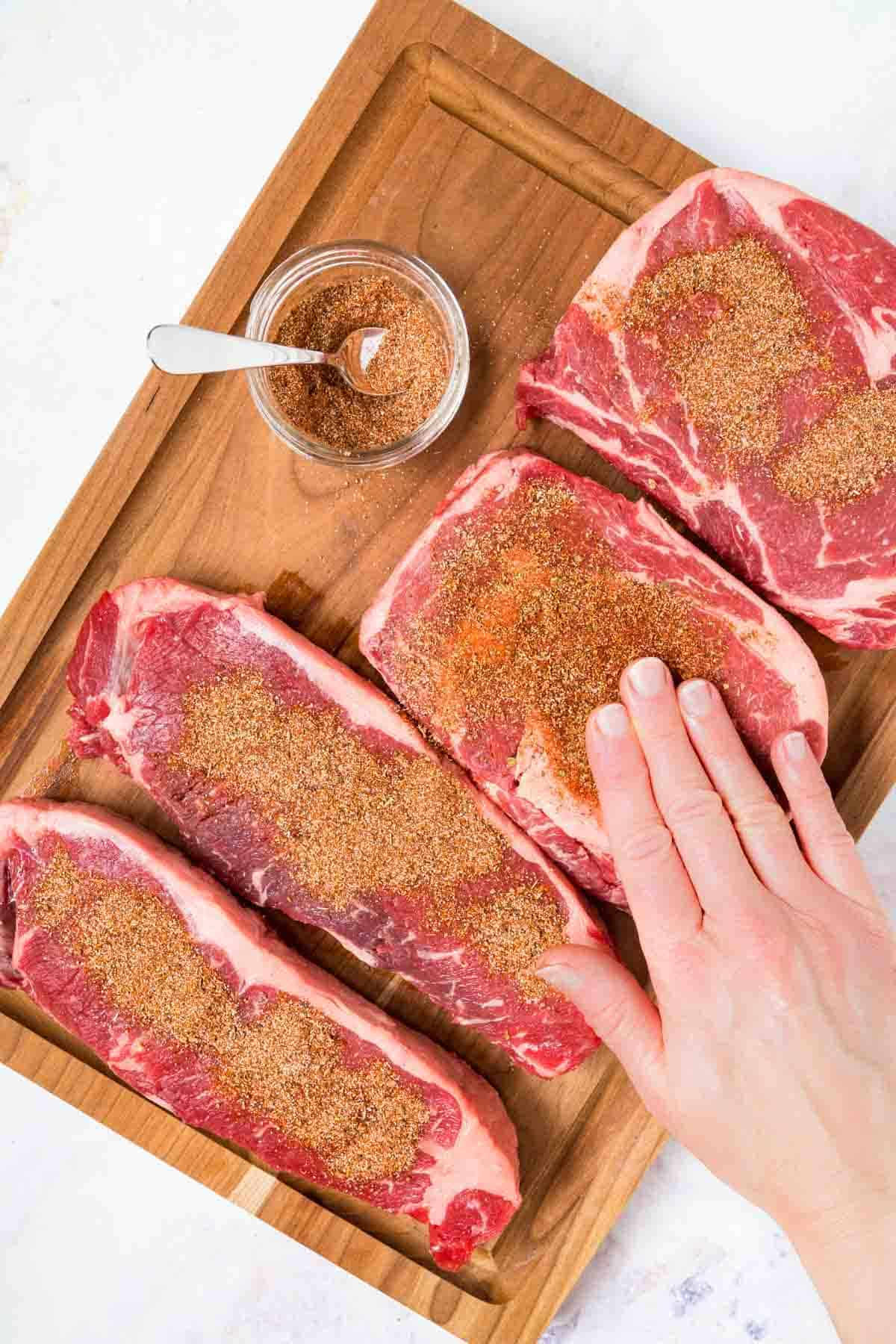 A Hand Rubbing the Spice Rub Onto Four Steaks on a Wooden Cutting Board