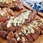 blackened grilled new york strip steaks and ribeyes topped with blue cheese on a cutting board, one of each sliced