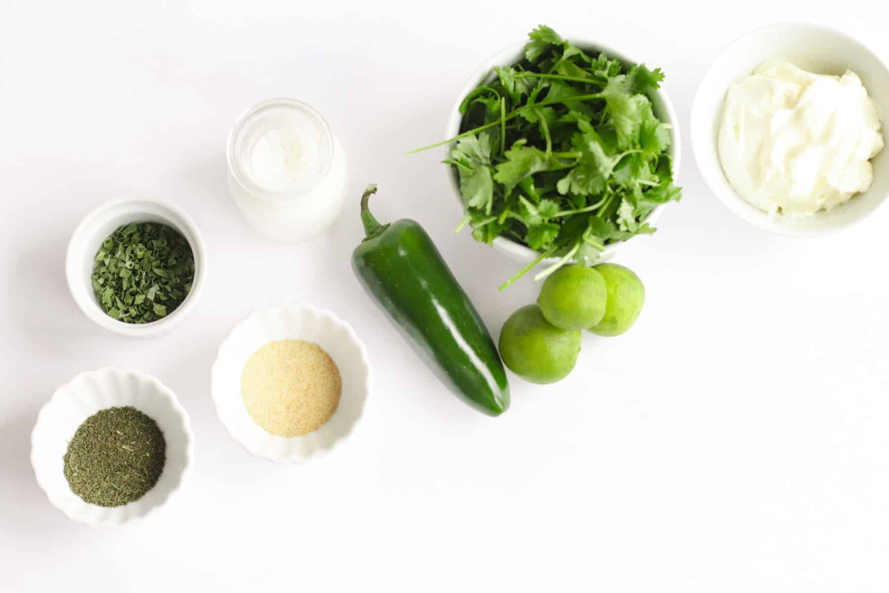 bowls of chives, dill, garlic powder, milk, mayonnaise, cilantro, limes, and jalapeno on a white tabletop