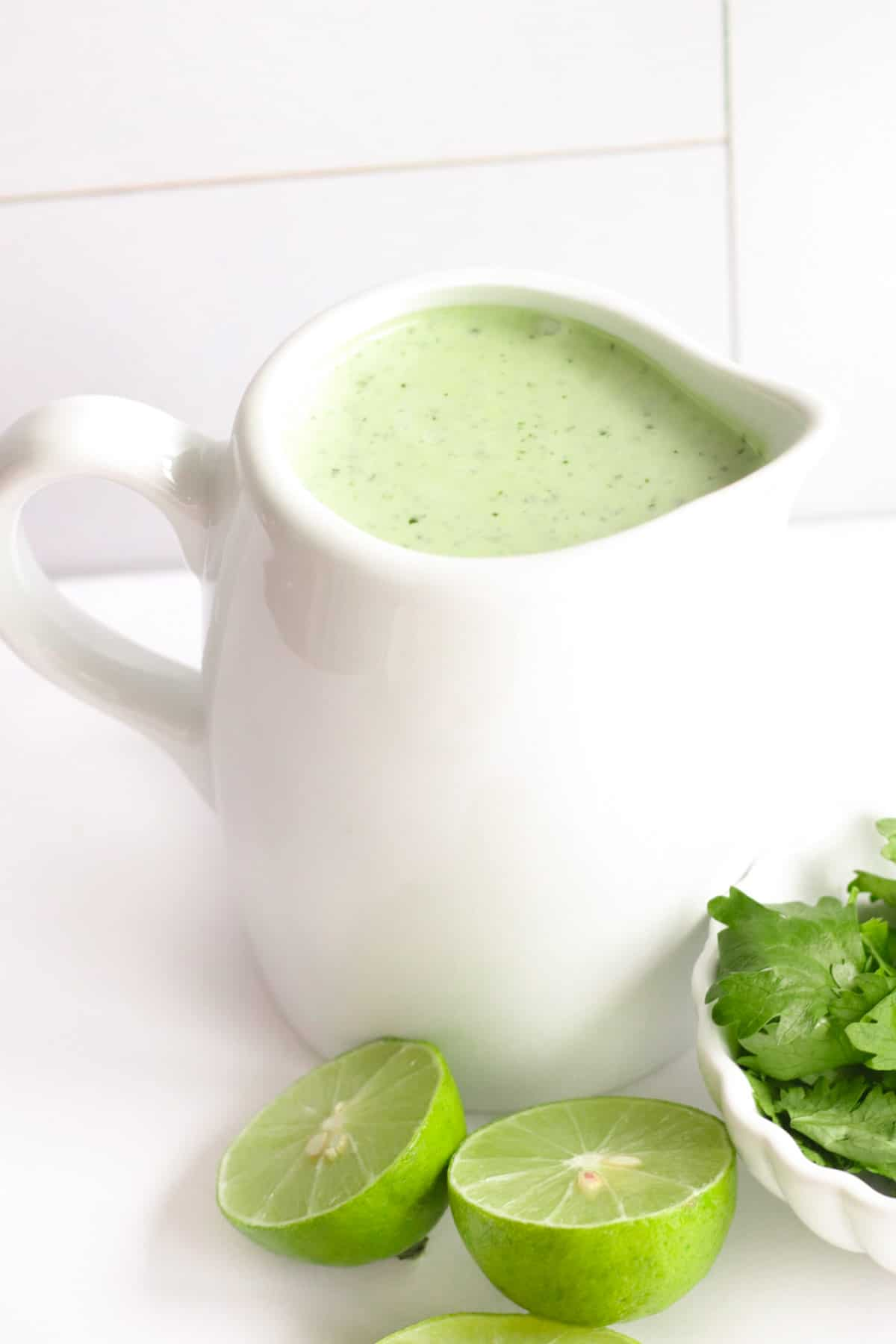 jalapeno ranch dressing in a white container for pouring nest to a dish of cilantro and limes