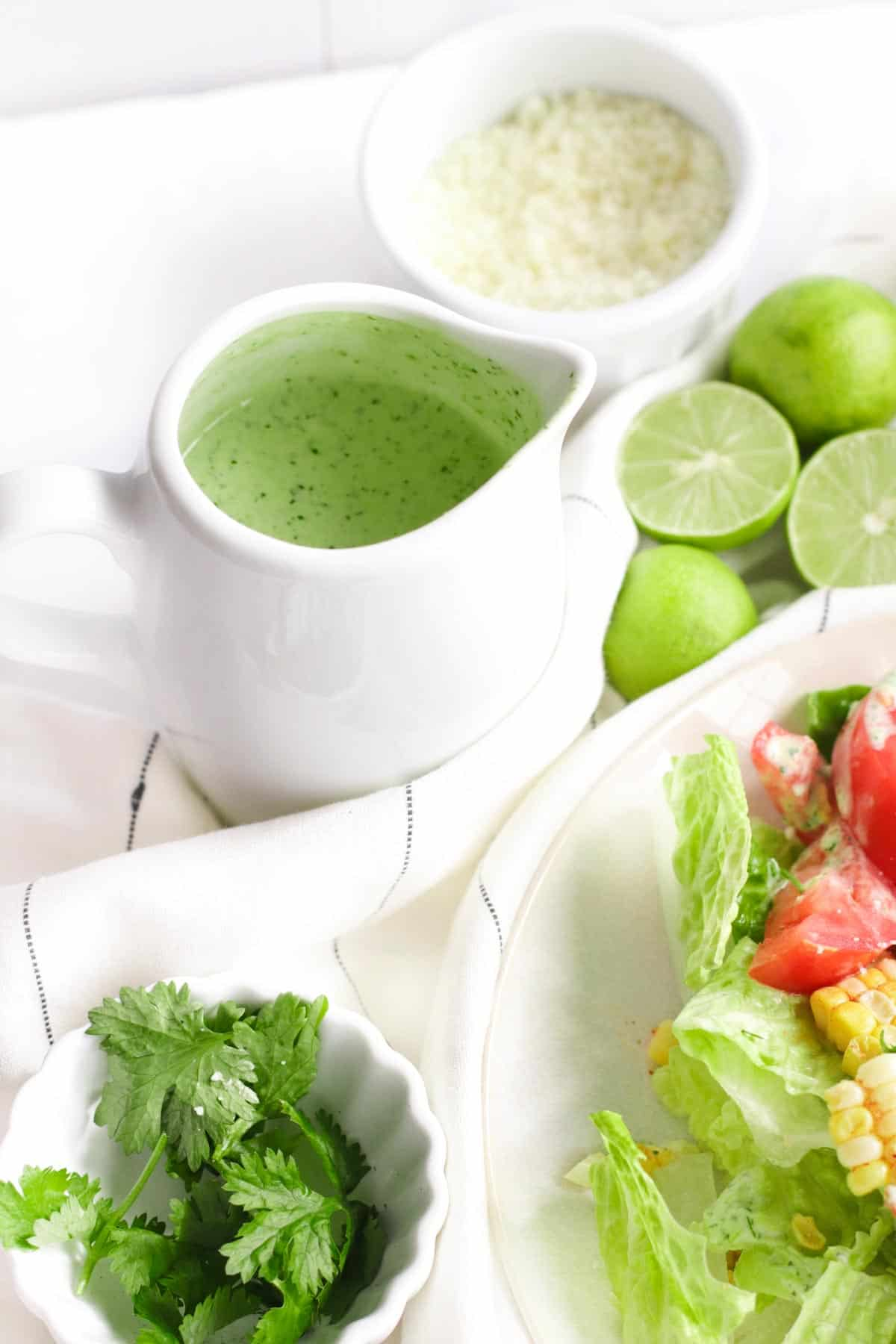container of dressing, bowls of salad and cilantro, and lime nestled in a napkin on a table