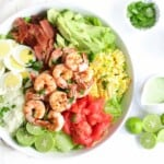 grilled shrimp cobb salad in a serving bowl with lime halves, a container of salad dressing, and a bowl of cheese next to it