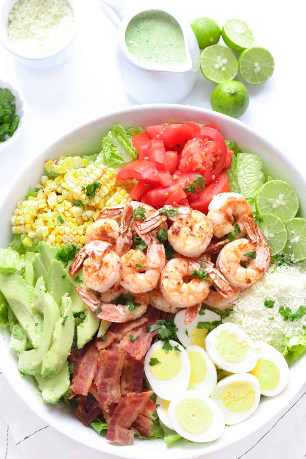 Shrimp Cobb Salad with hard boiled eggs, bacon, limes, tomatoes, avocado, cotija cheese, grilled corn, in a white serving bowl with a pitcher of cilantro lime dressing next to it