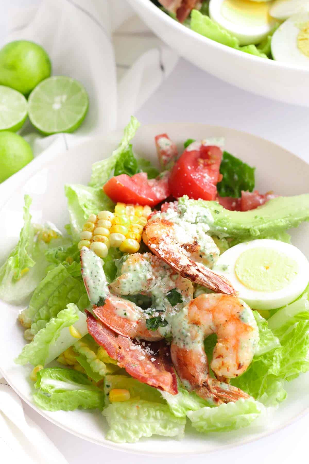 serving of the grilled shrimp salad on a small white plate with the shrimp topped with a drizzle of dressing
