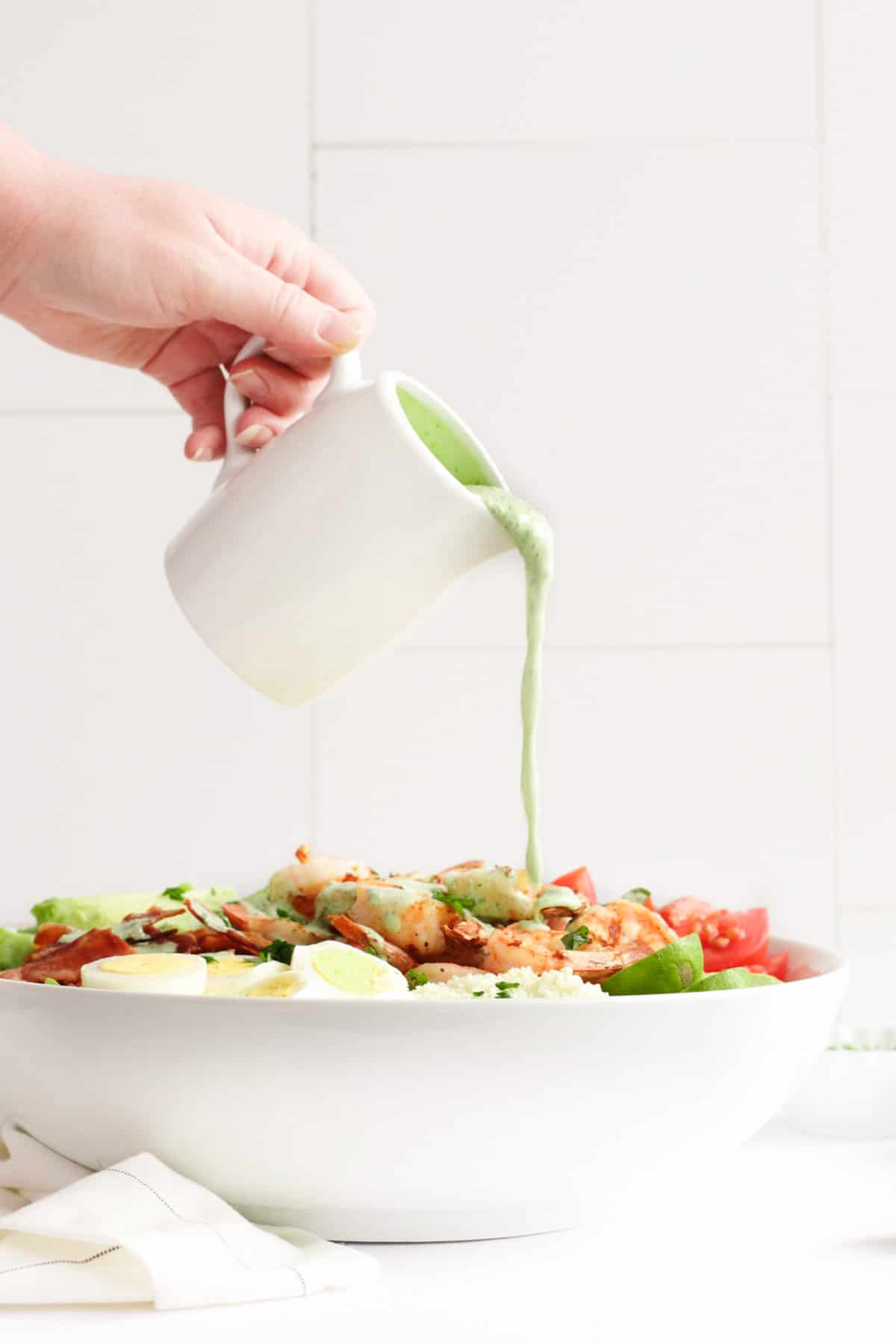 pouring cilantro lime ranch dressing over the grilled shrimp salad in a large bowl