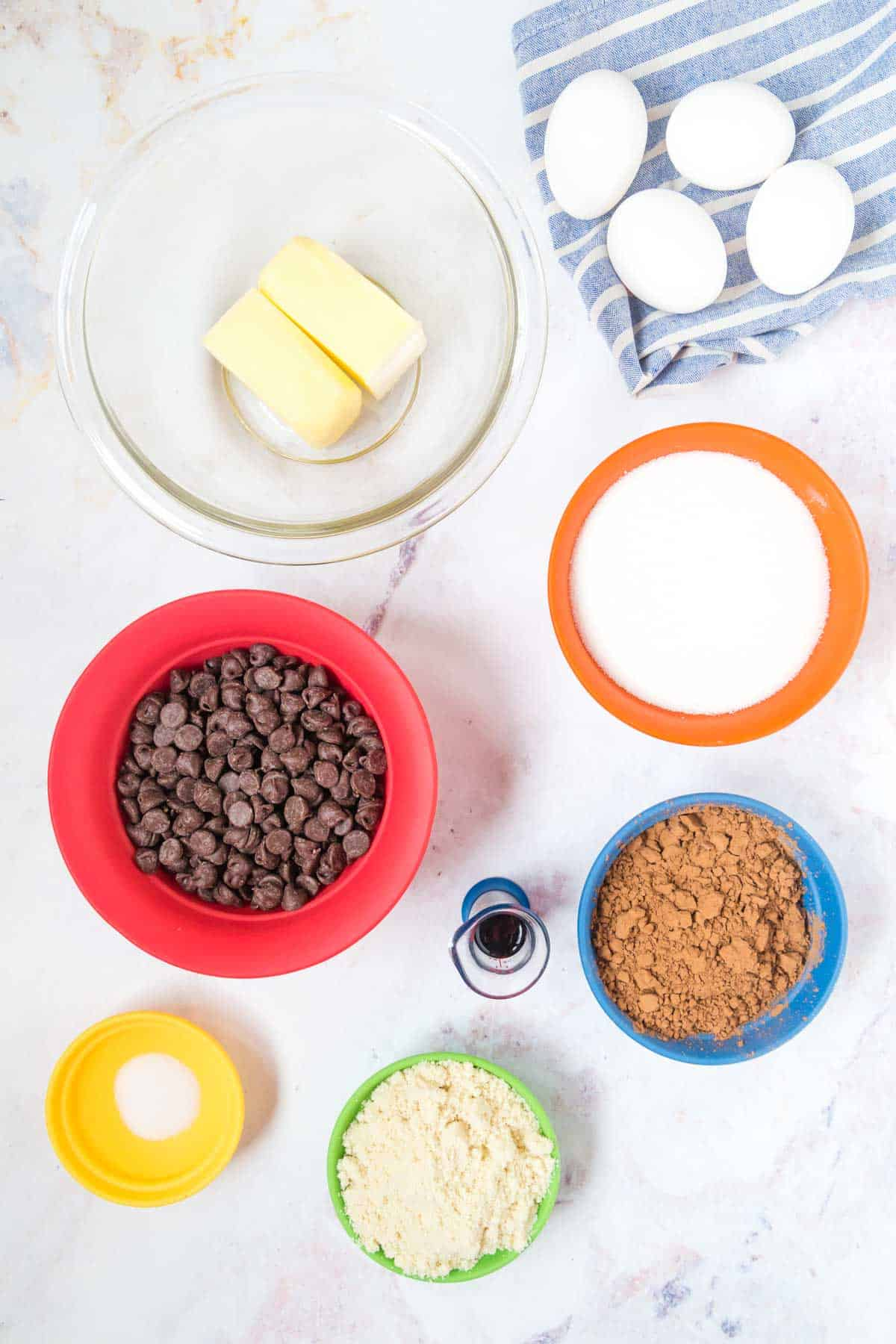 bowls of chocolate chips, butter, sugar, salt, cocoa powder, vanilla extract, and almond flour plus four eggs on a napkin on a marble tabletop