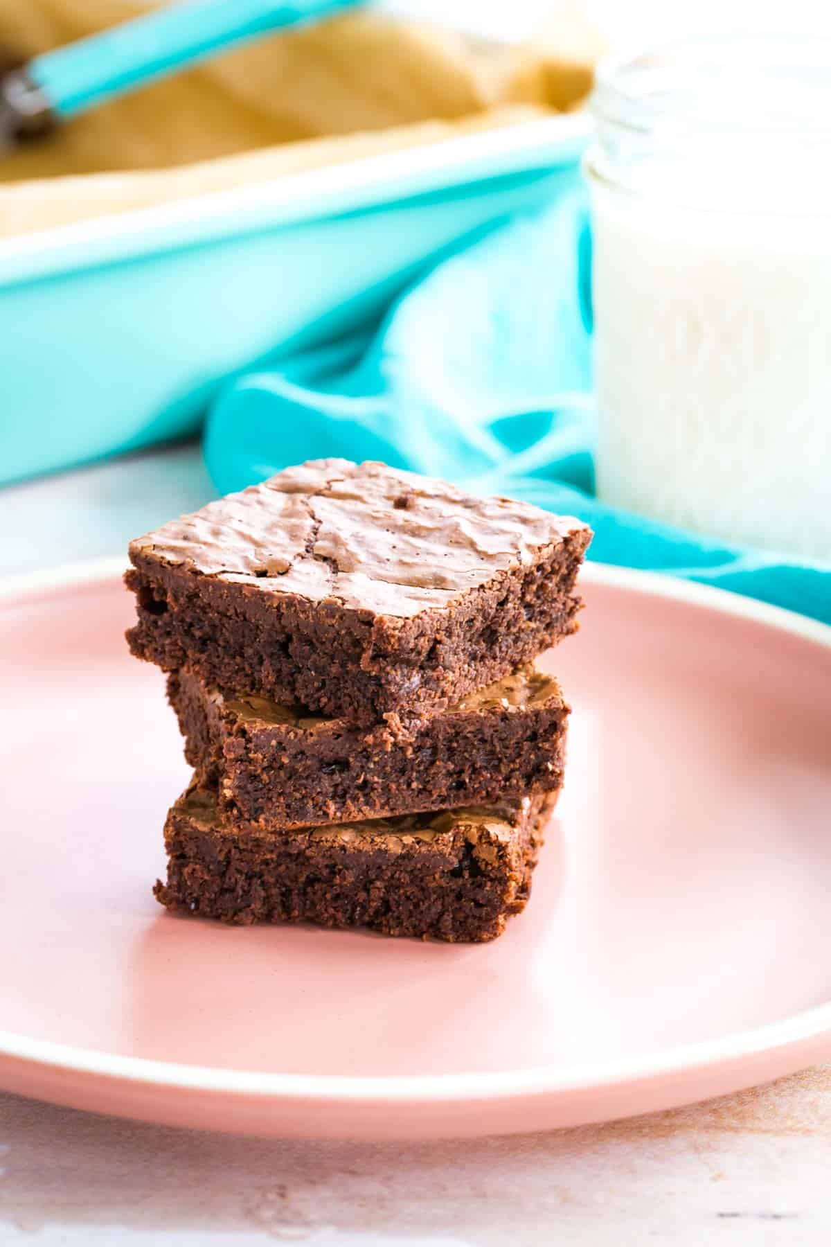 three thin brownies on a pale pink plate