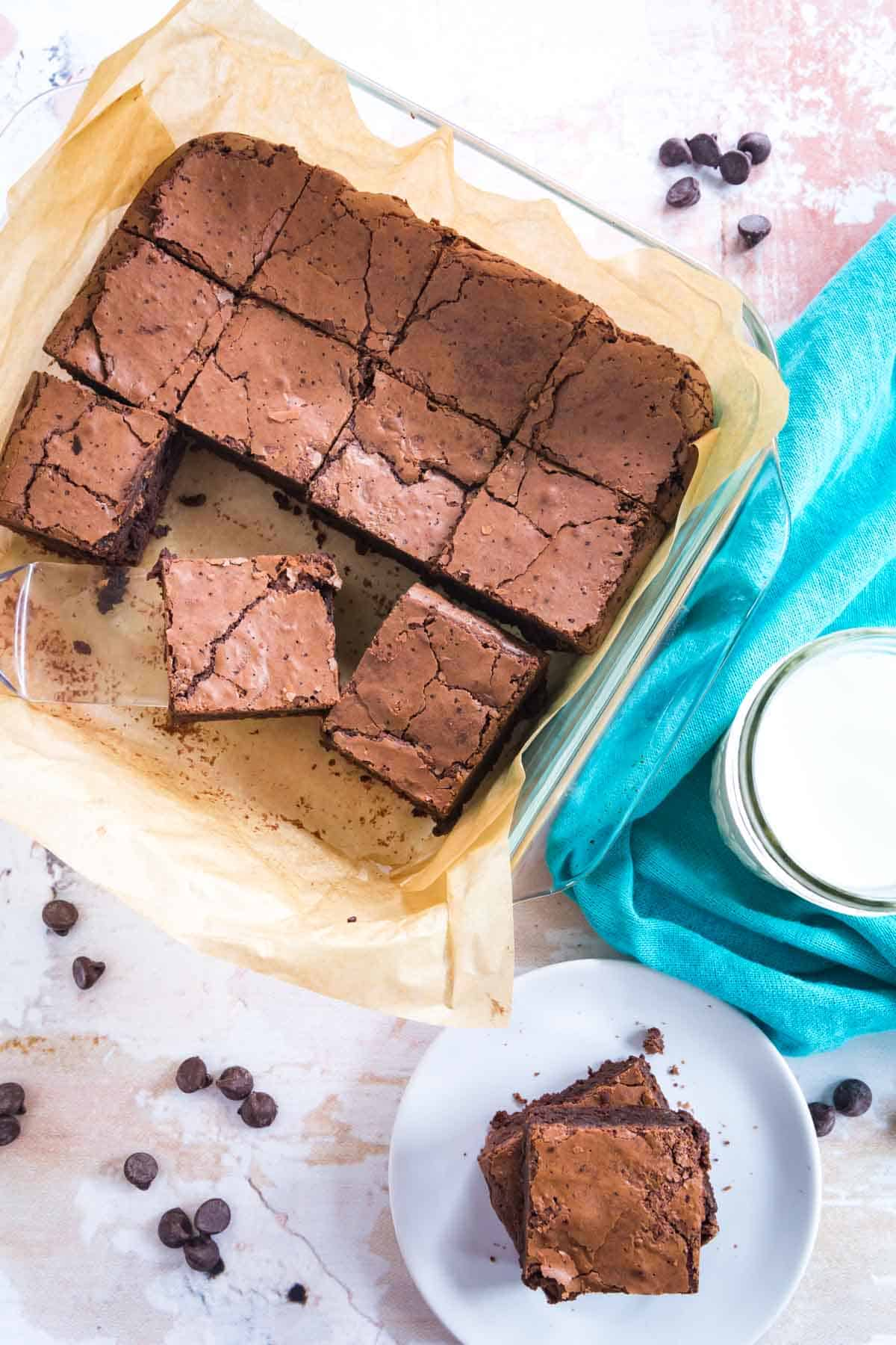 square glass baking dish with brownies in it and two of the brownies on a plate with a glass of milk