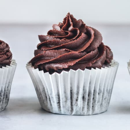 three chocolate cupcakes with chocolate frosting in a line