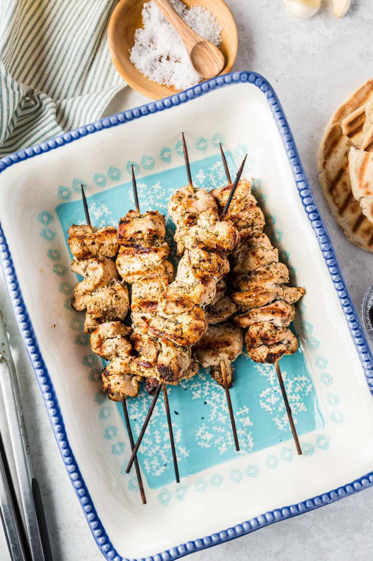 Freshly Grilled Chicken Souvlaki Beside a Kitchen Towen and a Small Dish of Salt